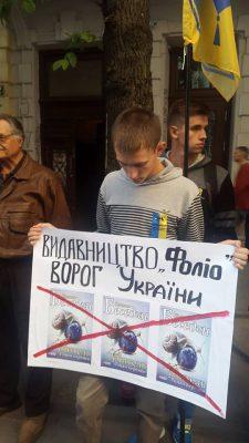 """Учасник мітингу тримає плакат """"Видавництво ФОЛІО - ворог України"""""""